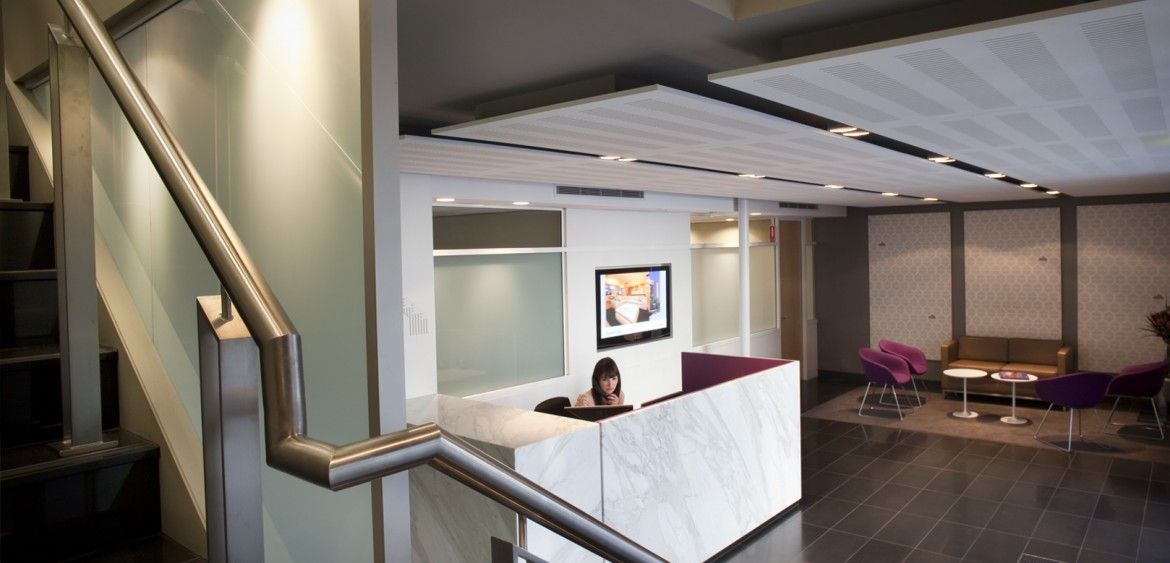 Reception area at Richard Crookes Constructions, taking in the staircase, receptionist sitting at the desk and waiting area with seating in the rear of the image