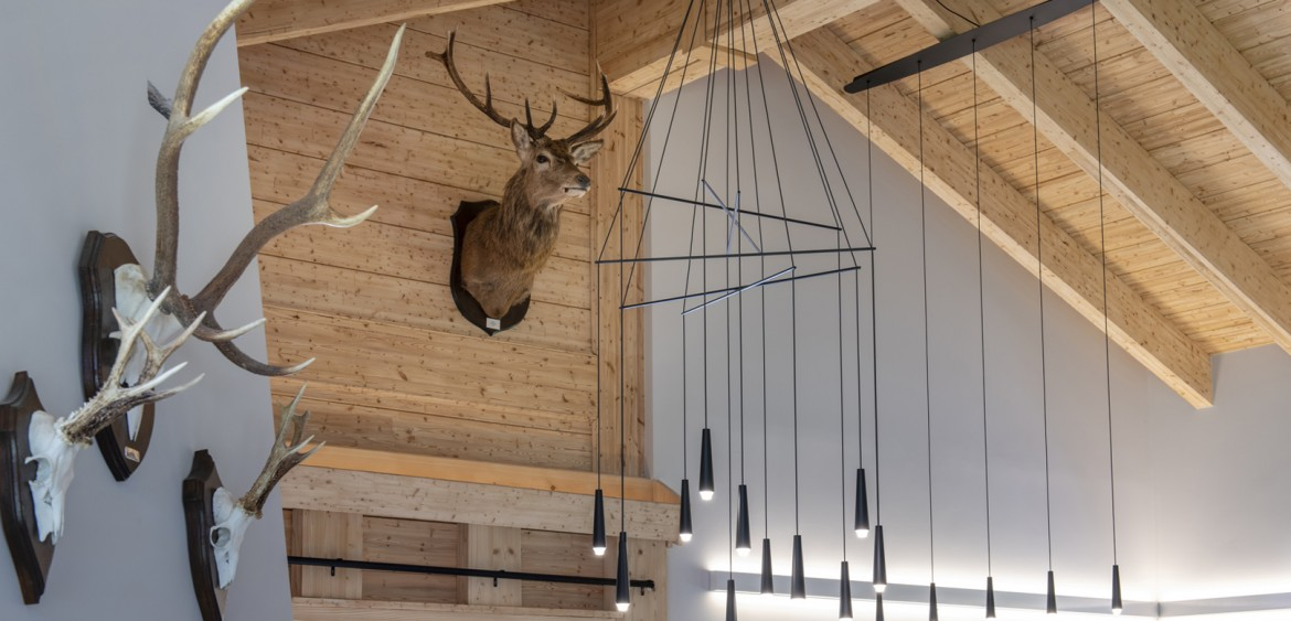 Stag head and other mounted horns at the Le Châble private residence with lighting over the table